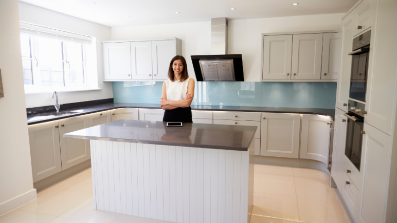 rental property manager standing behind kitchen bench in rental property